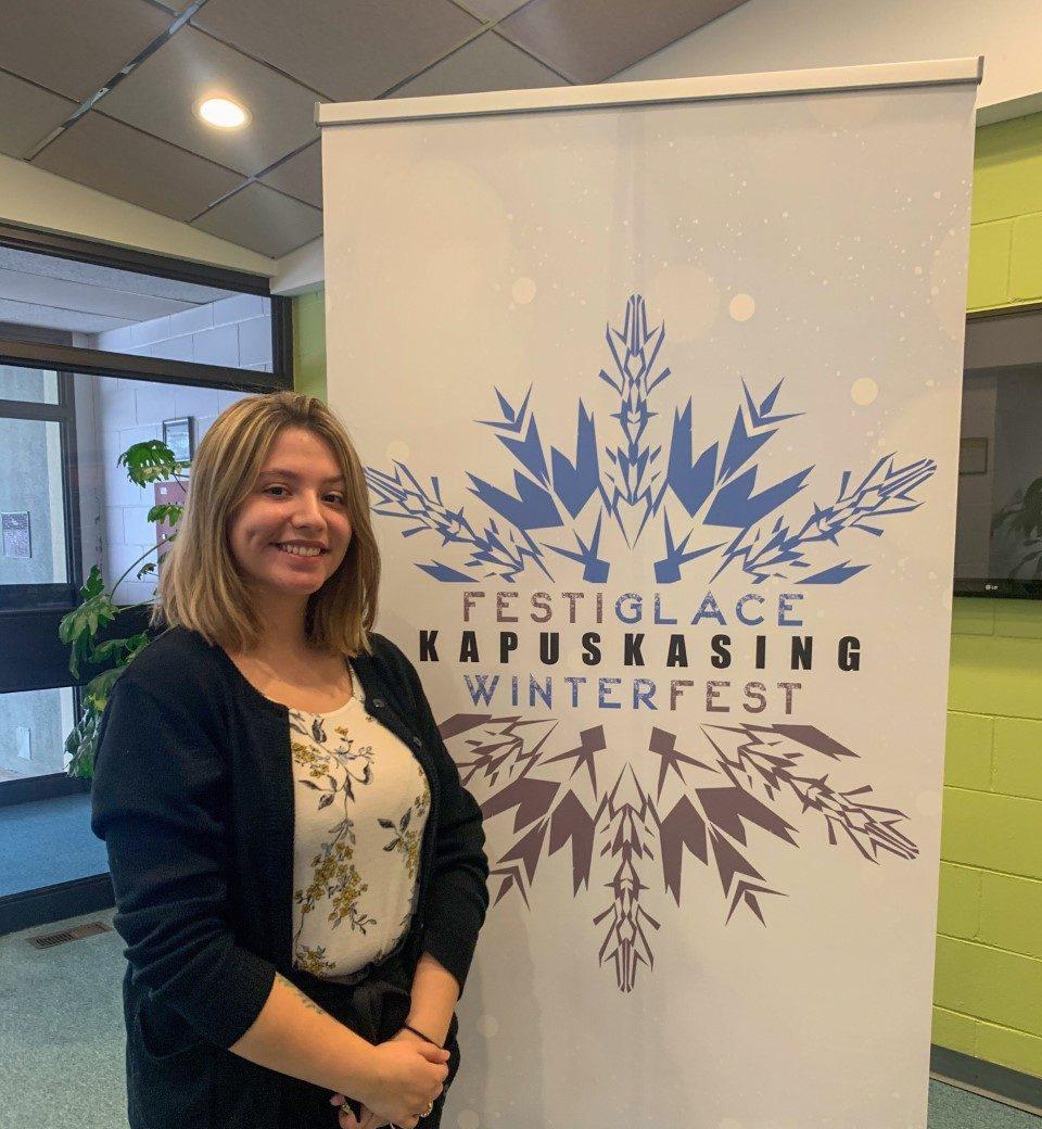 Alexia Brazeau qui travaille au Centre de loisirs devant le logo du Festiglace